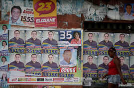 A woman walks past election posters during municipal elections in Sao Luis, Brazil, Oct. 2, 2016.