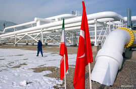 A worker walks past the pumping station on the border between Iran and Turkey during the inauguration ceremony for the Iran - Turkey gas pipeline, January 22, 2002.