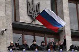 FILE - In this March 5, 2014 file photo, pro-Russia demonstrators holding a Russian flag, with the Ukrainian emblem in the background, stand on the balcony of the regional administrative building after storming it in Donetsk, Ukraine