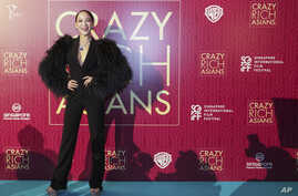"Actress Fiona Xie poses for photographers as she arrives for the red carpet screening of the movie ""Crazy Rich Asians,"" Aug. 21, 2018, in Singapore."
