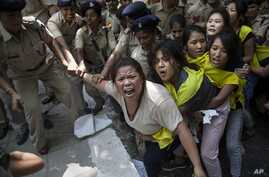 Indian policewomen detain Tibetan youth activists during a protest to highlight Chinese control over Tibet, outside the Hyderbad House in New Delhi, India, Sept. 18, 2014.