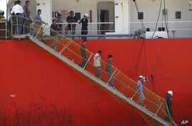 FILE - Afghan migrants walk down the stairway of a tanker that rescued them at a port in Cilegon, Banten province, Indonesia, Monday, April 9, 2012. Indonesia said it had rescued 120 Afghan migrants from a leaking wooden ship headed to Australia afte