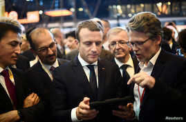 French President Emmanuel Macron (C) holds a device at the Viva Technology event dedicated to start-ups development, innovation and digital technology in Paris, June 15, 2017.