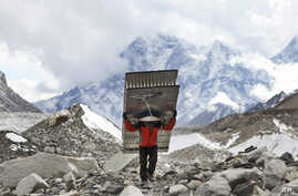 In this March 7, 2016 photo, a porter fetches the ladders for the icefall doctors who will be fixing the route for the climbers trying to attempt the summit of Mt Everest this year at Everest Base Camp in Nepal.