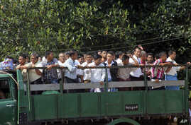 Myanmar prisoners ride a truck as they were released from Insein prison Tuesday, Oct. 7, 2014.