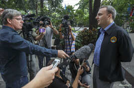British rights activist Andy Hall speaks to the media as he arrives for his trial at the Phra Khanong Provincial Court in Bangkok, September 2, 2014.