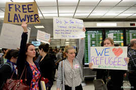 Lawyers offer free counseling as they join dozens of pro-immigration demonstrators cheering and holding signs as international passengers arrive at Dulles International Airport to protest President Donald Trump's travel ban in suburban Washington, Ja