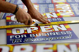 "Tom Cushing, a production expert at Fast Signs, cuts down a sheet of anti-Senate Bill 1062 signs that read ""Open For Business To Everyone,"" in Phoenix, Arizona, Feb.26, 2014."