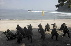 FILE - U.S. Marines from the 3rd Marine Expeditionary Brigade and the 31st Marine Expeditionary Unit and Philippine marines take their positions as they take part in a boat raid exercise during their joint military exercise, dubbed PHIBLEX 2016.
