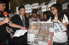 Director of Hong Kong Economic, Trade and Cultural Office, John Leung, center left, listens to Hong Kong student demonstrators, supporting pro-democracy protests taking place in Hong Kong, at the Hong Kong Economic, Trade and Cultural Office in Taipe