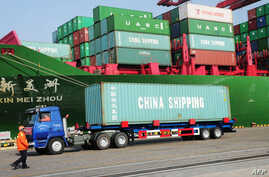 A truck transporting a container leaves the port of Qingdao, in northeast China's Liaoning province, Jan. 20, 2014.