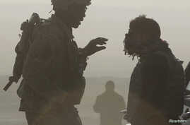 FILE - A US soldier and a translator are silhouetted as they talk to each other at a joint US military and Afghan police checkpoint in Nangarhar province, eastern Afghanistan.