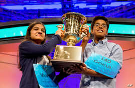 Vanya Shivashankar, left, 13, of Olathe, Kan., and Gokul Venkatachalam, 14, of St. Louis, hold up the championship trophy as co-champions after winning the finals of the Scripps National Spelling Bee, Thursday, May 28, 2015.