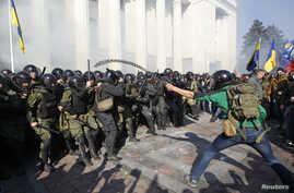Radical protesters, right, clash with Interior Ministry and law enforcement members on the Day of Ukrainian Cossacks during a rally near the parliament building in Kiev, Oct. 14, 2014.