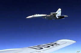 In this image released by the U.S. Air Force, a U.S. RC-135 flying in international airspace over the Baltic Sea is intercepted by a Russian SU-27 jet, June 19, 2017. The Russian military said it scrambled a fighter jet to intercept and escort a U.S.