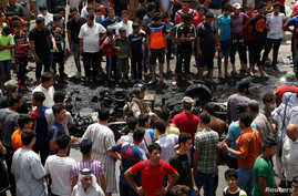 People gather at the scene of a car bomb attack in Baghdad's mainly Shi'ite district of Sadr City, Iraq, May 11, 2016.