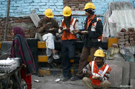 FILE - Laborers eat during a break from their work at the site of a commercial building under construction in Noida, on the outskirts of New Delhi, Dec. 13, 2013.