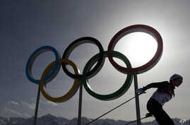 FILE – A skier passes by the Olympic rings at the 2014 Win