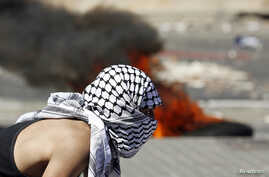 A Palestinian stone-thrower stands near a burning tire during clashes with Israeli police in Shuafat, an Arab suburb of Jerusalem, July 2, 2014.