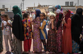"FILE - Women and children stand in line for food at Dibaga camp for internally displaced civilians in Iraq, Aug. 7, 2016. Some say the announcement about the return of refugees is politically driven in order to make the battle for Mosul ""appear more"