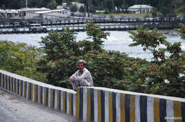 FILE - A man sits on a boundary wall near the Indus river in Gilgit.