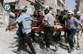 FILE - In this photo, provided by the Syrian Civil Defense White Helmets, rescue workers work the site of airstrikes in the al-Sakhour neighborhood of the rebel-held part of eastern Aleppo, Syria, Sept. 21, 2016. Violence in Aleppo has surged in rece...