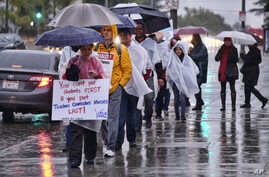 Los Angeles teachers walk on a picket line in pouring rain in front of Los Angeles High School during a city-wide teacher strike on Jan. 14, 2019.