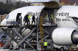 Investigators board a United Parcel Service jet isolated on a runway at Philadelphia International Airport in Philadelphia, Friday, Oct. 29, 2010.