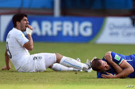 Uruguay's forward Luis Suarez (L) reacts past Italy's defender Giorgio Chiellini during a Group D football match between Italy and Uruguay at the Dunas Arena in Natal during the 2014 FIFA World Cup, June 24, 2014.