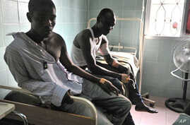 Wounded men receive medical care at a hospital in Abidjan's Treichville neighborhood on March 8, 2011