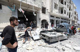 FILE - Syrians gather at a site of car bomb in the northwestern Syrian city of Idlib, Aug. 2, 2018.