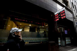 A man watches dollar rates outside an exchange house in Buenos Aires, Argentina, Aug. 30, 2018. Argentina's Central Bank increased its benchmark interest rate to 60 percent Thursday as the peso hit a new all-time low.