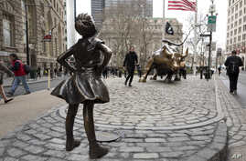"""A statue titled """"Fearless Girl"""" faces the Wall Street bull, Wednesday, March 8, 2017, in New York.   A big investment firm, State Street Global Advisors, put the statue there to highlight International Women's Day.  The work by artist Kristen Visbal."""