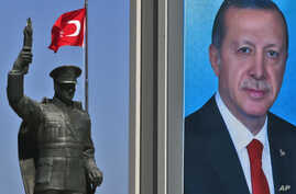 A statue of modern Turkey's founder Mustafa Kemal Ataturk and a poster of Turkey's President Recep Tayyip Erdogan for the upcoming referendum is seen in his hometown city of Rize, April 4, 2017.