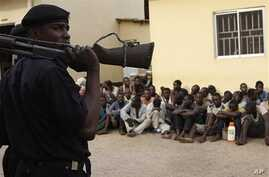 Policeman stand guard as suspected rioters await a court hearing in Kaduna, Nigeria, April 20, 2011