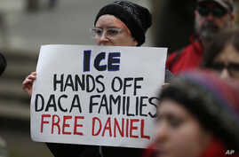"A protester holds a sign that reads ""ICE Hands Off DACA Families Free Daniel,"" during a demonstration in front of the federal courthouse in Seattle, Feb. 17, 2017."