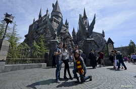 """Guests pose before they enter Hogwarts School during a soft opening and media tour of """"The Wizarding World of Harry Potter"""" theme park at the Universal Studios Hollywood in Los Angeles, California March 22, 2016."""