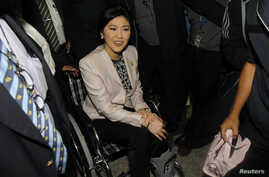 Thai Prime Minister Yingluck Shinawatra is helped in a wheelchair as she arrives at the National Anti-Corruption Commission office in Nonthaburi province, on the outskirts of Bangkok, March 31, 2014.