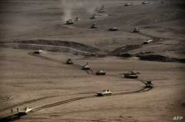 A convoy of tanks and armoured vehicles of the Iraqi army's 34th brigade advances near Talul al-Atshana, on the southwestern outskirts of Mosul, on Feb. 27, 2017, during an offensive to retake the city from Islamic State (IS) group fighters.