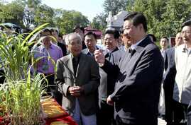In this photo released by Xinhua News Agency, Chinese Vice President Xi Jinping, front right, attends an activity to mark this year's National Science Popularization Day at China Agricultural University in Beijing, September 15, 2012.