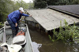 Florence, S.C., resident Jackie Lee surveys the flooding to his property along the Lynches River near Effingham, S.C., where houses and cars are swamped following record rainfall in the state, Oct. 6, 2015.