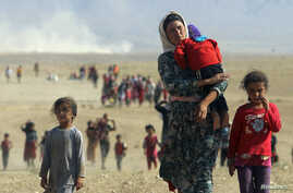 Displaced Yazidis, fleeing violence from forces loyal to the Islamic State group, head toward the Syrian border Aug. 11, 2014.