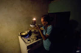 "Mireya Marquez uses candlelight to cook her dinner of boiled ""cassava,"" also known as yuca and manioc, Aug. 19, 2018, during a blackout in Maracaibo, Venezuela. For months Maracaibo's residents have endured rolling blackouts, but things turned dire A"