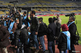 "Egyptian photojournalists hold their cameras during a silent protest against preventing them by the officials from covering the Egyptian Premier League derby soccer match between Al-Ahly and El Zamalek at Borg El Arab ""Army Stadium"", west of Alexandr"