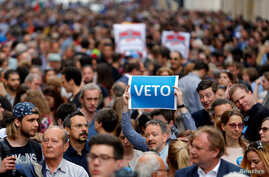 "A demonstrator holds up a banner saying ""Veto"" during a rally against a new law passed by Hungarian parliament which could force the Soros-founded Central European University out of Hungary, in Budapest, April 4, 2017"