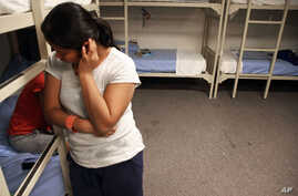 FILE - An unidentified Guatemalan woman and a child are seen inside a dormitory in the Artesia Family Residential Center, a federal detention facility for undocumented immigrant mothers and children in Artesia, New Mexico, Sept. 10, 2014.