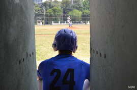 A Cuban baseball player watches action on the field at the 50th Anniversary Stadium in Cuba.