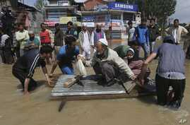 Kashmiri men use a makeshift raft to evacuate an elderly man and his grand daughter from a flooded neighborhood in Srinagar, India, Sept.7, 2014.