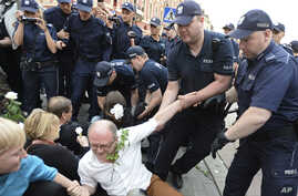 Polish police remove protesters staging an anti-government demonstration in Warsaw, Poland,, June 10, 2017. The demonstrators attempted to block a group led by Jaroslaw Kaczynski, leader of the ruling conservative Law and Justice party, commemorating