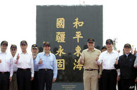 """Taiwan's President Ma Ying-jeou, fifth from left, poses for a group photo in front of a monument reading: """"Peace in the East China Sea and our national territory secure forever"""" during his visit to Pengjia Islet in the East China Sea, north of Taiwan"""
